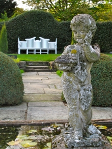 Cherub statue with white garden