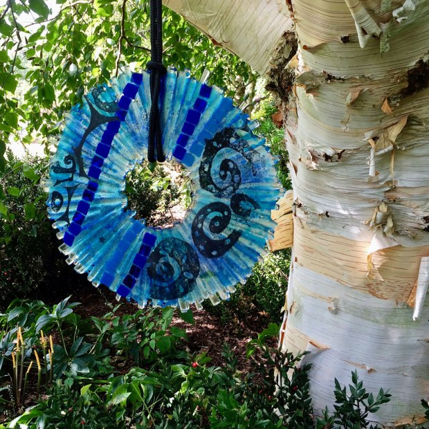 Blue glass disk hanging from a tree