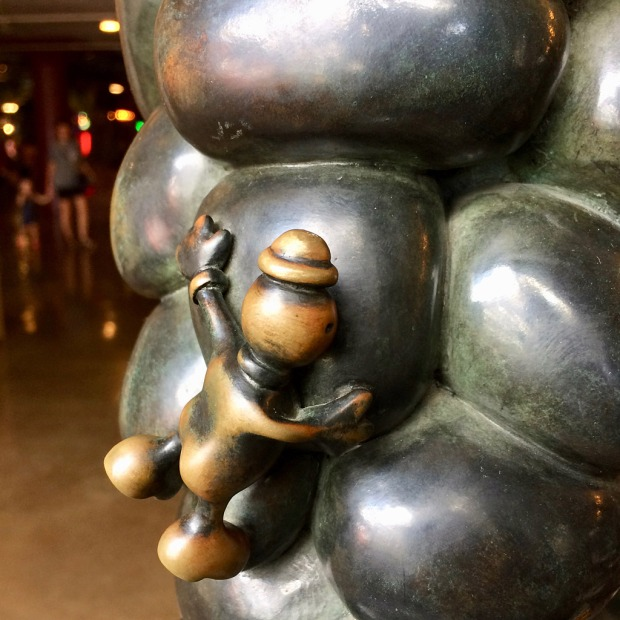 Sculpture of a little man clinging to bubble shaped metal