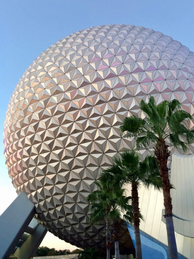 A globe shaped structure towers above palm trees