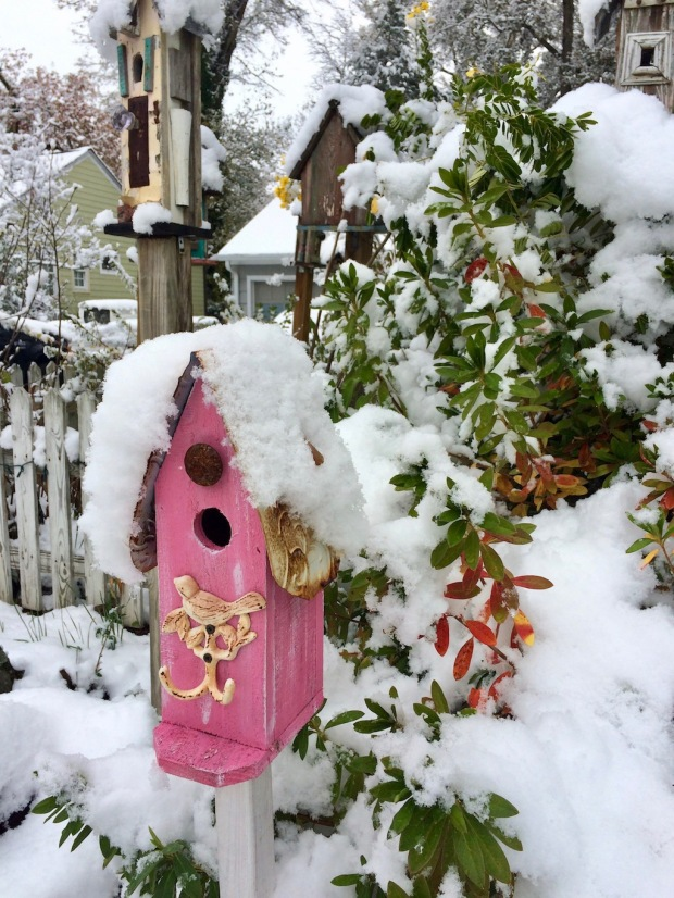 Pink birdhouse with a covering of snow