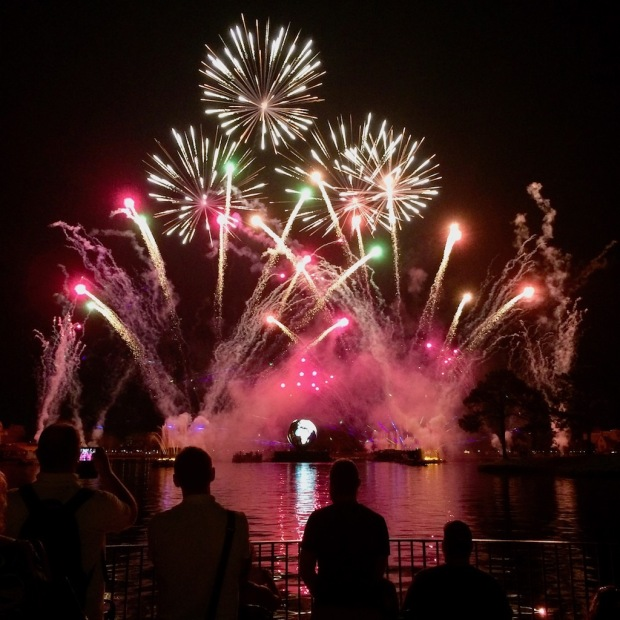 People watching an evening firework display at Epcot