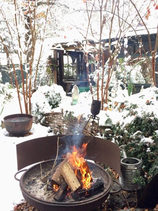 Logs burning in a fire pit in a snowy landscape