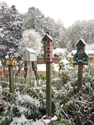 Four birdhouses in a snowy garden