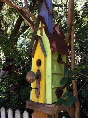 A lime green bird house with a tin roof and yellow door
