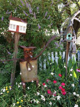 A rusty tin man in a flower garden