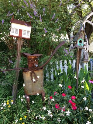 A rusty tin man in a flower garden