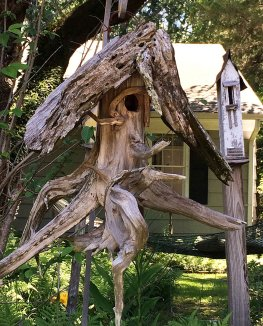 A bird house made from a tree stump with roots