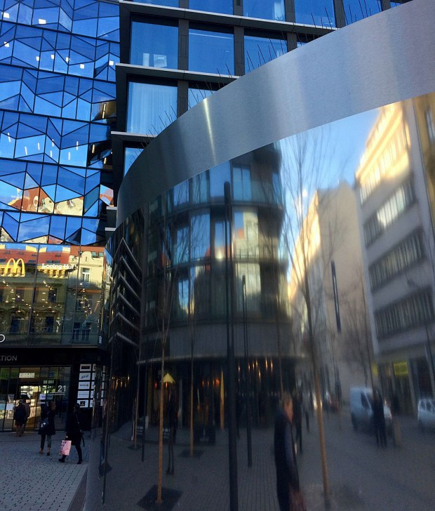 Buildings, people and cars reflected in a metallic surface