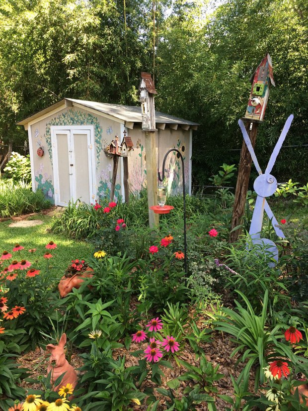 A hand-painted garden hut with flowers and garden art