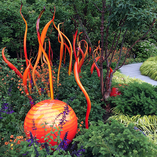 Glass orb and long squiggles in a garden