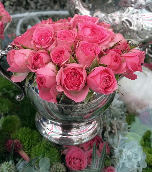 Twenty four small pink rose buds clustered in a milk jug