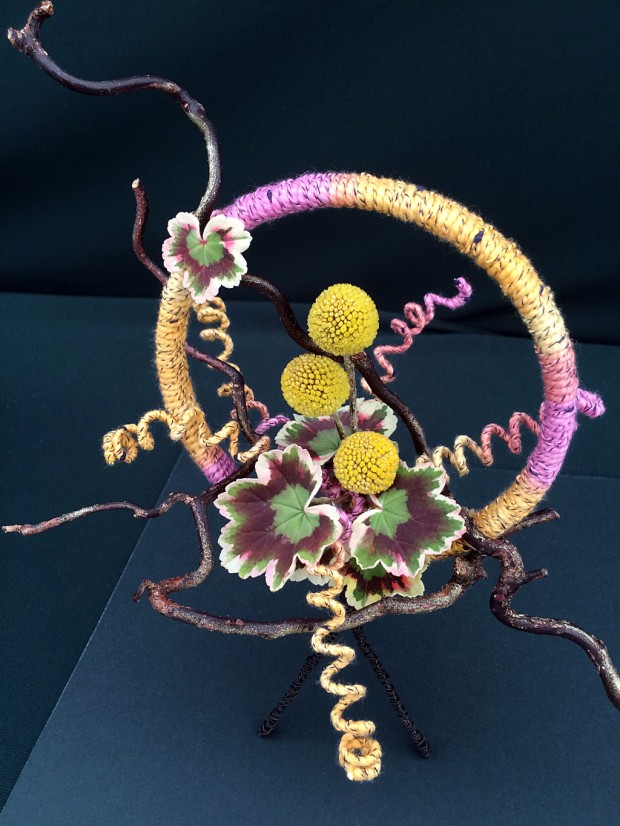 A floral design with wool, twigs, small leaves and yellow pom poms