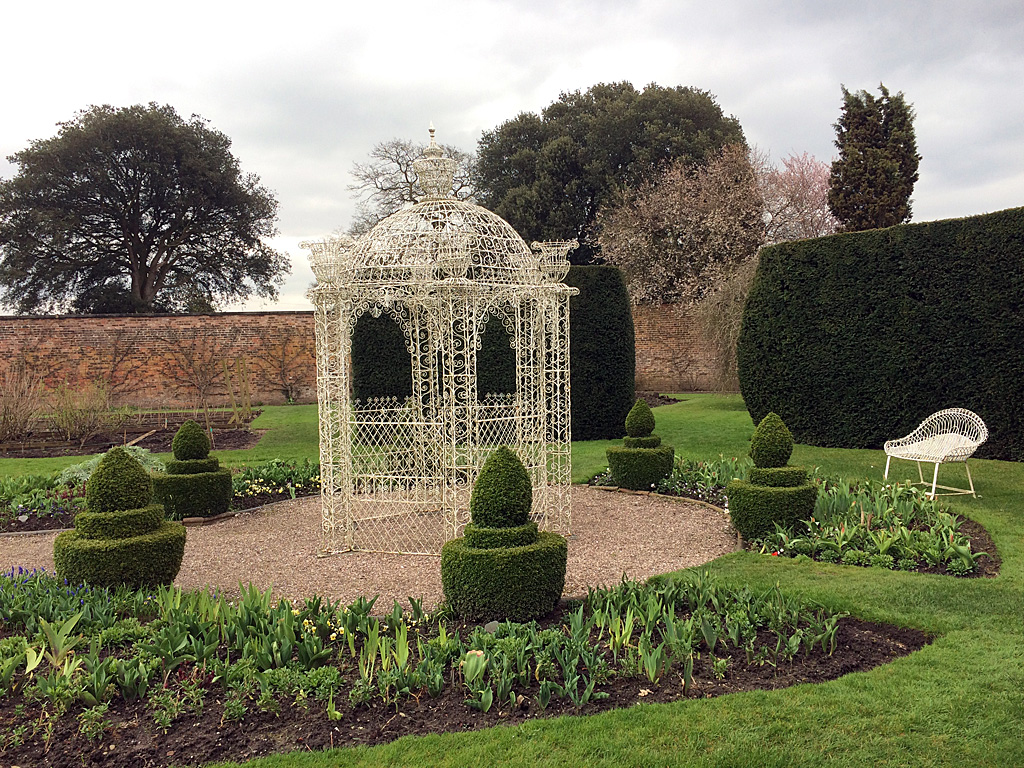 White wire gazebo in a formal garden with topiary