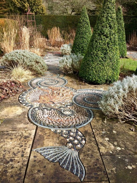 A swirl design pebble path leads through a winter garden