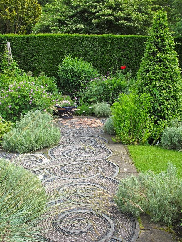 A swirl-effect stone path, flanked by greenery