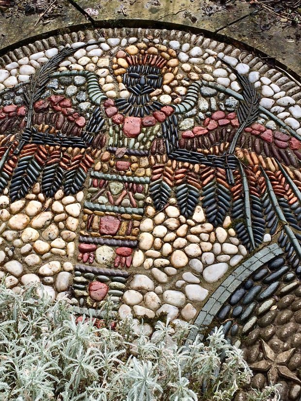 A lady with headdress, wings and dress made from coloured pebbles