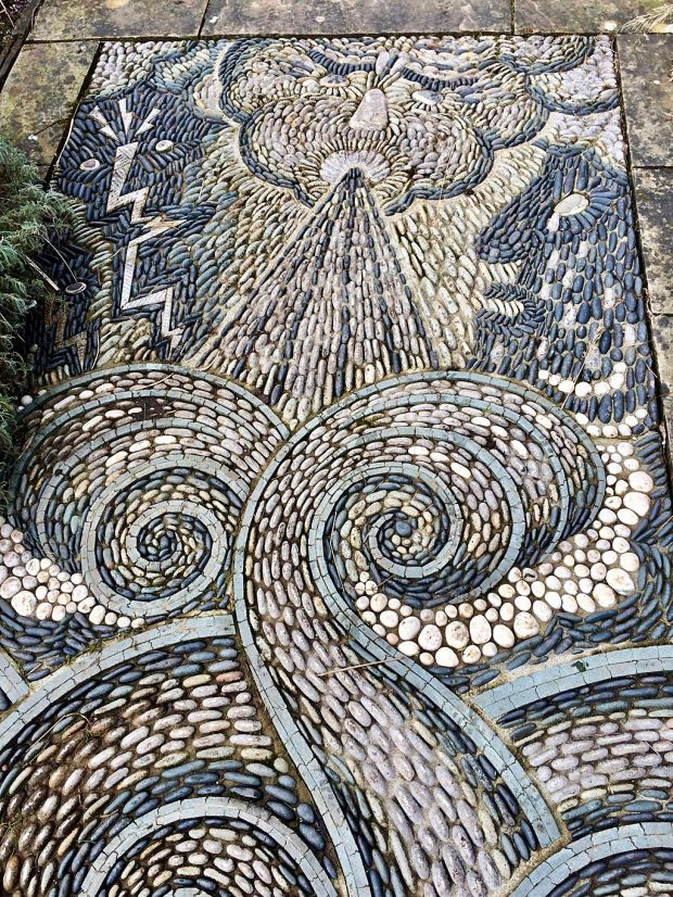 Swirl pebble path with image of a man blowing to create the winds