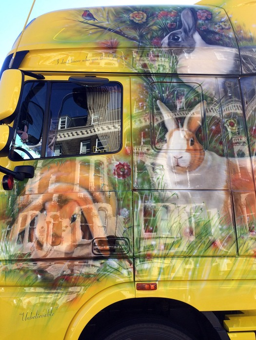 Shiny side view of yellow lorry with rabbit design and reflections
