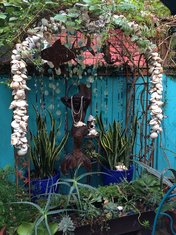 Container garden with mermaid under a shell arch