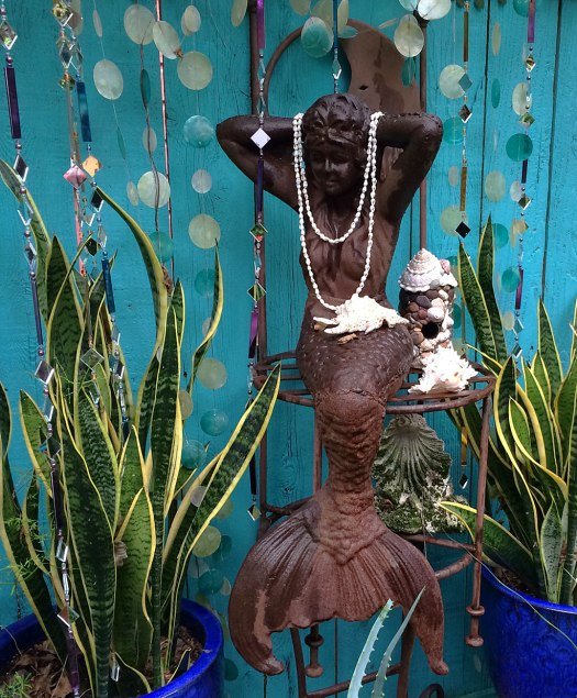 Mermaid with pearl necklace, shells and plants