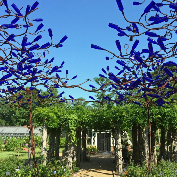 Tree-shaped wire frames covered in blue bottles
