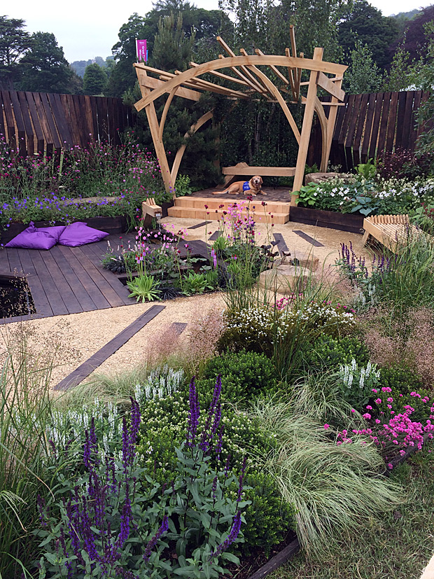 Garden with wooden arbour and purple flowers