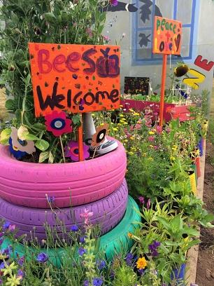 Signs in a flower bed with pink, purple and turquoise tyre planter