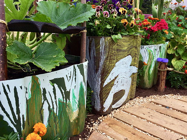 Plastic wheelie bin style planters with abstract designs