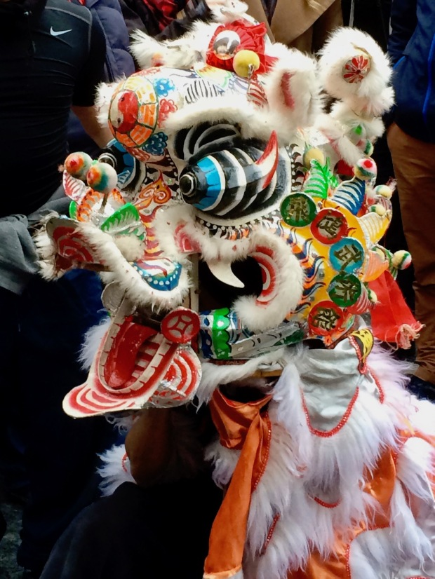 Colourful lion mask with protruding eyes and wide open mouth