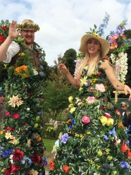 Man and lady on stilts in flower and leaf costumes