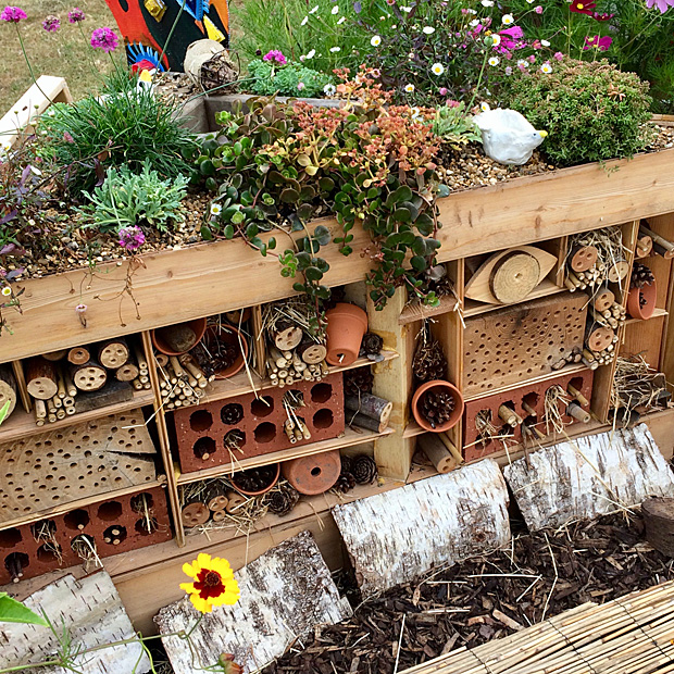 Bug hotel with bored wood, straw and flowerpots and bricks