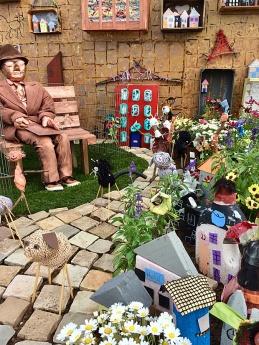 Bronze man on a bench in a fantasy garden