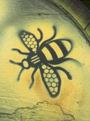 Black bee motif picked out with yellow spray paint
