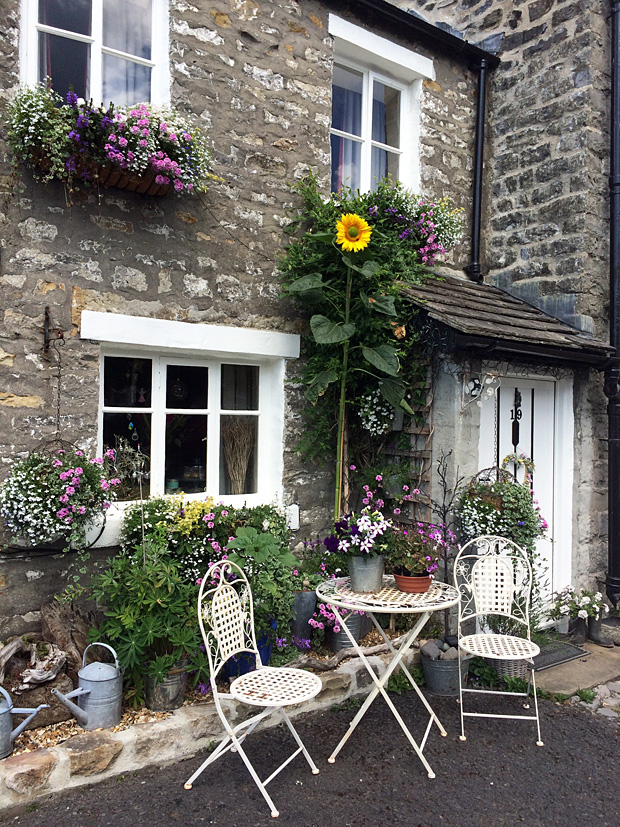 A seating area outside a terraced house with flowers