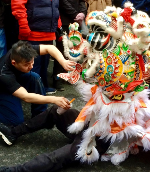 Lion dancer being offered a drink