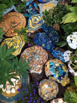 Tree trunk segments decorated in blues and yellows