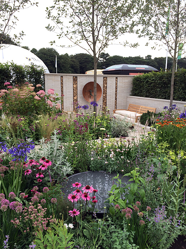 Garden packed with flowers, water feature and seating