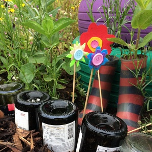 Wine bottles edge a path, wellington boot flower pots and tyre planter