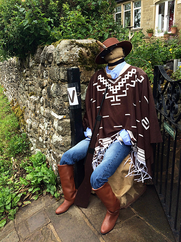 Scarecrow in blue jeans with a poncho, hat and cigar