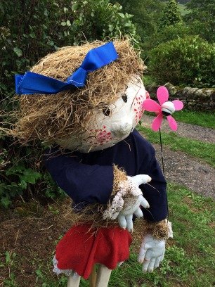 Scarecrow with pink cheeks, a blue ribbon and a flower