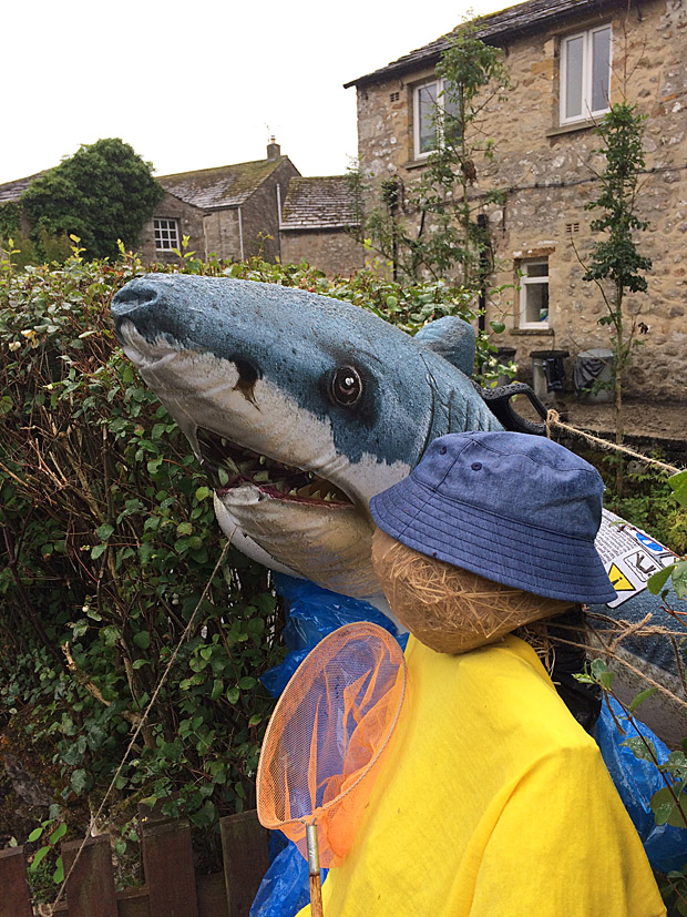Scarecrow carrying a fishing net with a large shark