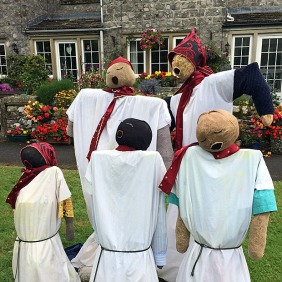 Five scarecrows singing in front of a colourful garden
