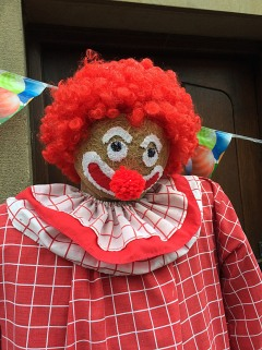 Smiling clown with red curls and red checked costume