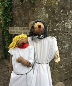 Male and female chorister scarecrows beside a church signpost