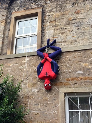 Spiderman hanging from a web on the side of a house