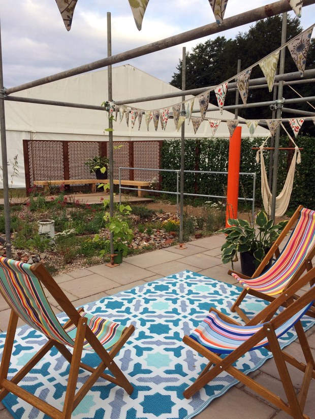Community garden on a brownfield site with deckchairs and bunting