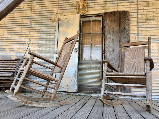 Rocking chairs on a wooden porch outside a tin shack