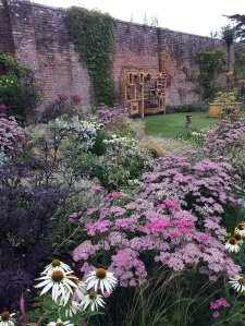 A walled garden with flowers and a wooden play stand