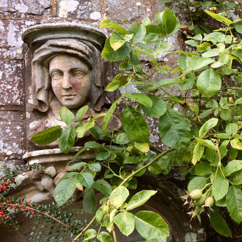 Stone carving of a veiled lady on a garden wall